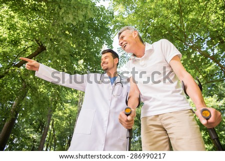 Cheerful doctor encouraging his patient to walk with crutches.