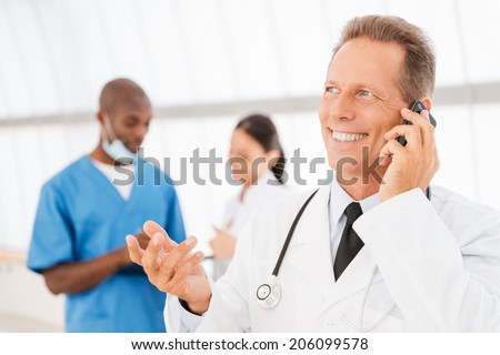 Cheerful doctor on the phone. Cheerful mature doctor talking on the mobile phone and gesturing while his colleagues talking in the background - stock photo