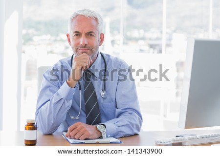 Cheerful doctor sitting behind his desk at the office - stock photo