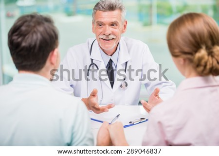 Cheerful doctor talking with family couple at clinic.
