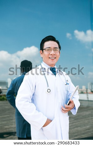 Cheerful doctor with tablet computer smiling and looking at the camera