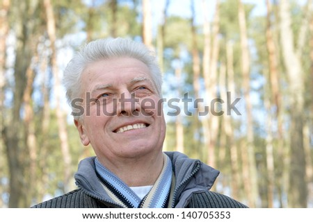 cheerful elderly man out for a walk in the park