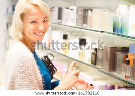 Cheerful elegant blond young woman testing cosmetics in perfumery. - stock photo