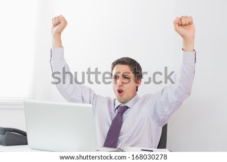 Cheerful elegant businessman cheering in front of laptop in a bright office - stock photo