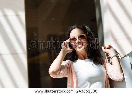 Cheerful elegant woman in sunglasses talking on the phone