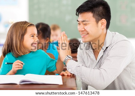 cheerful elementary school teacher and student high five in classroom - stock photo