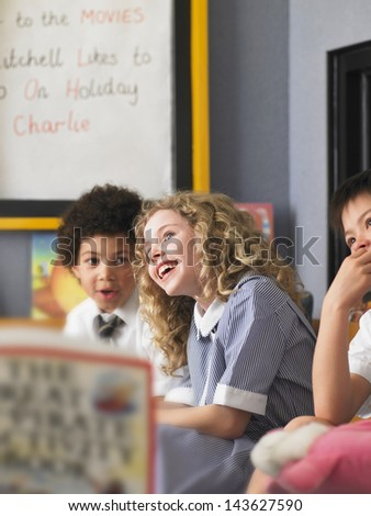Cheerful elementary schoolgirl with boys sitting in classroom - stock photo