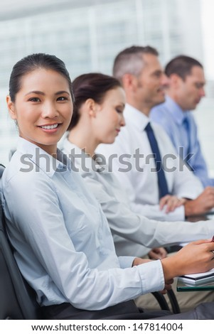 Cheerful employee attending presentation with her colleagues in bright office