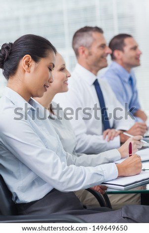 Cheerful employees attending presentation in bright office - stock photo