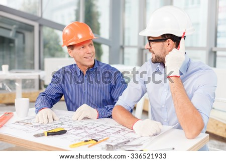 Cheerful engineers are designing the building. They are sitting at the table near a blueprint. The men in helmets are talking and smiling