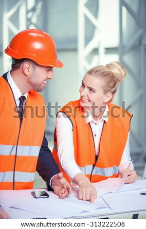 Cheerful engineers are planning to build new construction. They are standing near the table with blueprints. The workers are looking at each other and smiling. The man is wearing a helmet - stock photo