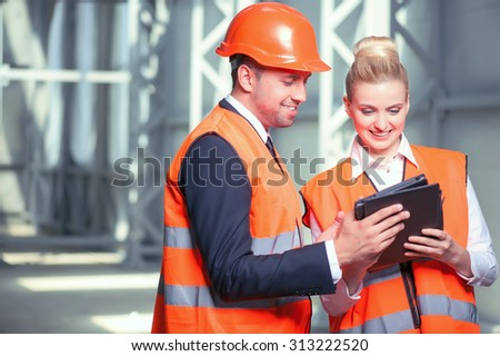 Cheerful engineers in workwear are discussing their project. They are holding a tablet and looking at it with concentration. The builders are smiling. Copy space in left side - stock photo