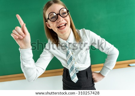 Cheerful enthusiastic pupil pointing with her finger up, telling the teacher know something - stock photo