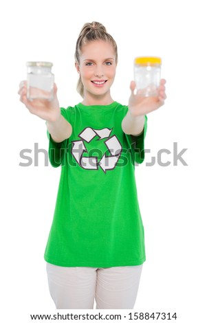 Cheerful environmental activist wearing recycling tshirt holding jars on white background - stock photo
