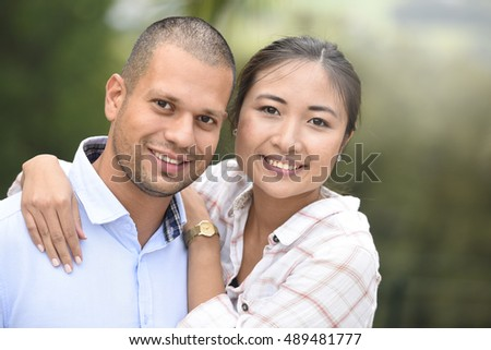 Cheerful ethnic couple embracing each other