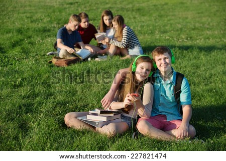 Cheerful European couple with earphones and cell phone outdoors - stock photo