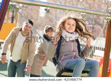 Cheerful european  family with two girls having fun on swings outdoors  - stock photo