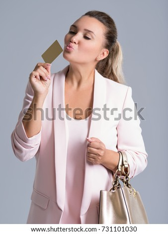 cheerful excited surprised young woman kissing credit card over white background