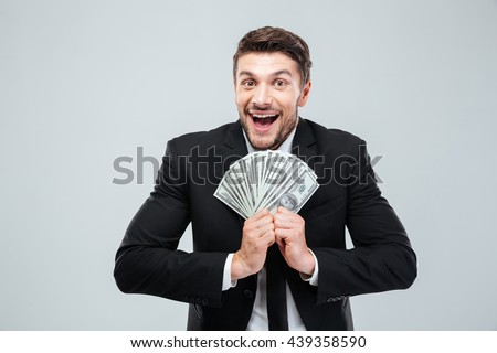 Cheerful excited young businessman laughing and holding money over white background - stock photo