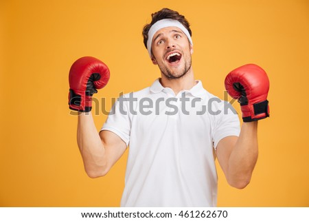 Cheerful excited young man boxer in red gloves shouting and celebrating success over yellow background