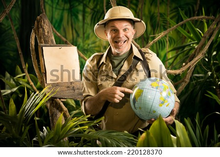 Cheerful explorer in the jungle pointing to a globe next to a wooden sign. - stock photo