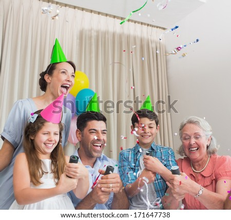 Cheerful extended family playing with Christmas crackers in the house - stock photo