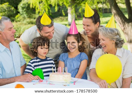 Cheerful extended family wearing party hats at a birthday celebration in the park - stock photo