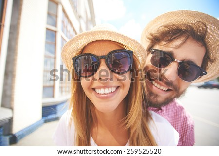 Cheerful faces of young couple - stock photo