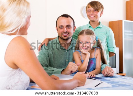 Cheerful family and advisor sitting at desk with documents