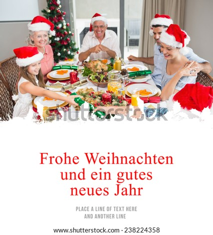 Cheerful family at dining table for christmas dinner against christmas greeting in german - stock photo