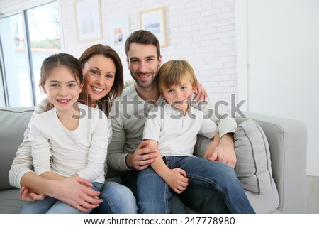 Cheerful family at home sitting in sofa - stock photo