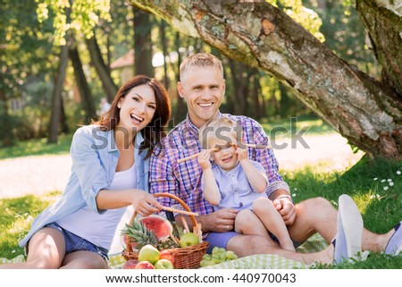 Cheerful family being really excited in the park. Child playing with pretzel sticks.