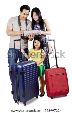 Cheerful family carrying luggage to holiday and looking an online map on the digital tablet - stock photo