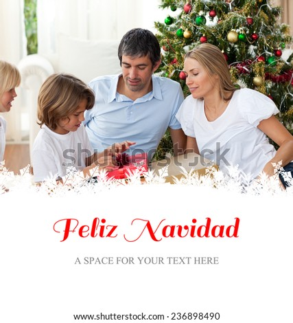 Cheerful family celebrating Christmas against feliz navidad - stock photo