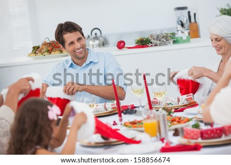Cheerful family dining together for christmas - stock photo