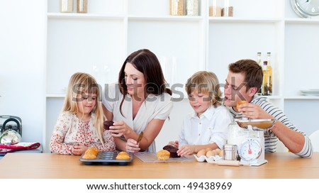 Cheerful family eating muffins in the kitchen at home - stock photo