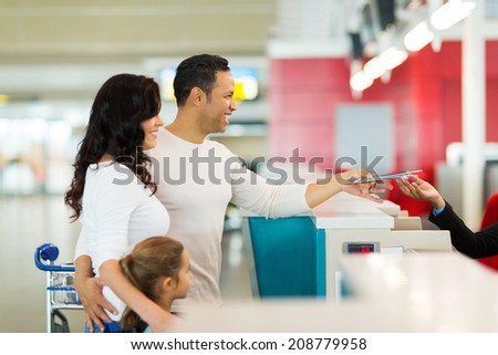 cheerful family handing over air ticket at airport at check in counter - stock photo
