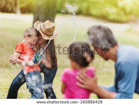 cheerful family having fun she does a water gun fight, mom and son against dad and daughter, focus on mom and her son - stock photo