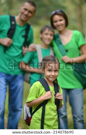 Cheerful family in green shirts walking in the summer park