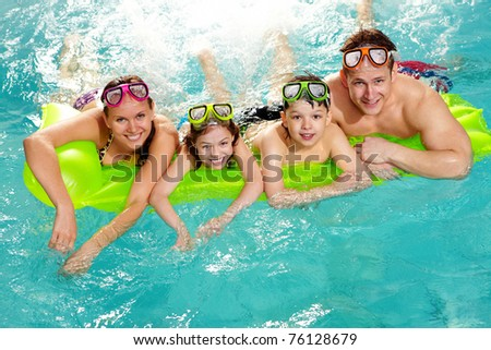 Cheerful family in swimming pool smiling at camera - stock photo