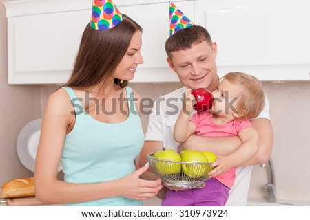 Cheerful family is making fun in kitchen. A man is holding his daughter gently. The child is eating apple with enjoyment. The husband and wife are looking at her and smiling - stock photo