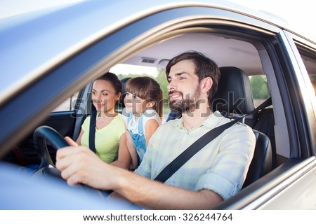 Cheerful family is making trip by car. They are sitting and smiling. The man is driving transport with joy. The mother and girl are looking forward with happiness