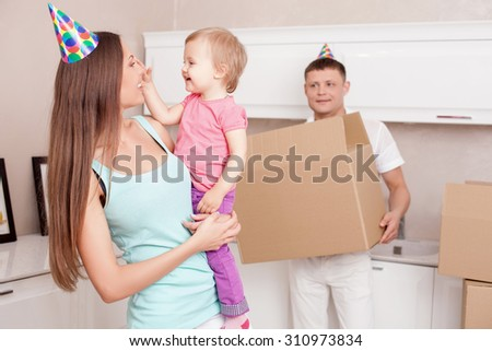 Cheerful family is packing things in their kitchen and smiling. They want to move in a new building. A woman is holding her daughter with joy. Her husband is holding a box - stock photo