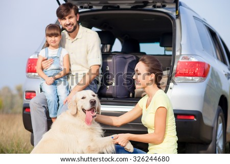 Cheerful family is resting in the nature and smiling. The father and his daughter are sitting in open car boot and embracing. The woman is kneeing and playing with dog - stock photo