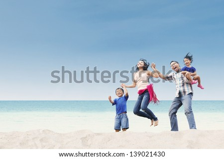 Cheerful family jumping at white sand beach - stock photo