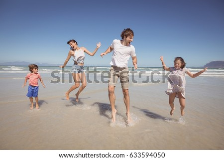 Cheerful family jumping on shore at beach against clear blue sky