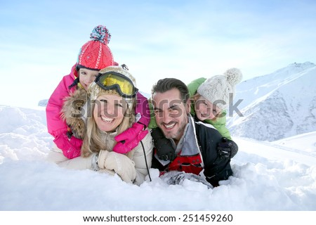 Cheerful family laid down in snow ground - stock photo