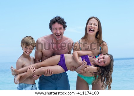 Cheerful family lifting girl while standing at sea shore against clear blue sky