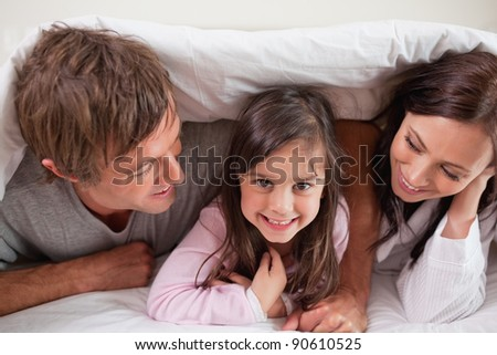 Cheerful family lying under a duvet in a bedroom - stock photo