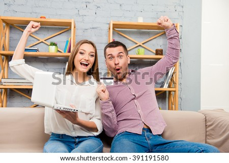 Cheerful family making internet shopping with laptop and bank card - stock photo